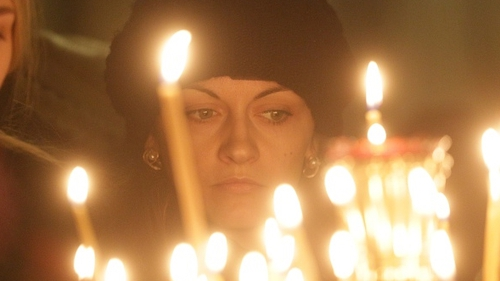 A woman attends memorial service in the memory of Russian airplane crash victims
