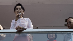 Aung San Suu Kyi delivers a speech from the balcony of the NLD headquarters in Yangon