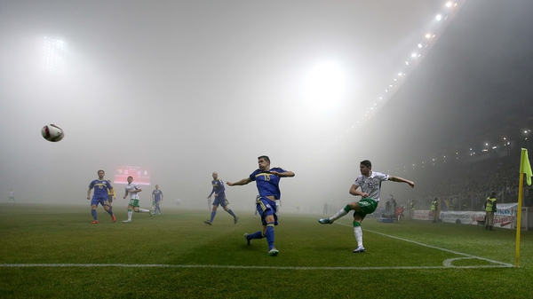 Ireland's Robbie Brady clears as a thick fog covers the pitch