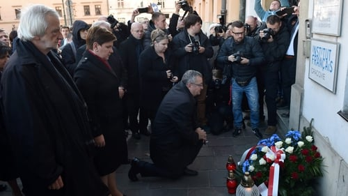 Polish Prime Minister designated Beata Szydlo (2L) places flowers in front of the French consulate