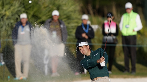 Kevin Kisner hits out of a bunker on the 17th hole
