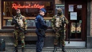A police officer and soldiers stand guard on the streets of Brussels following the terror alert level being raised