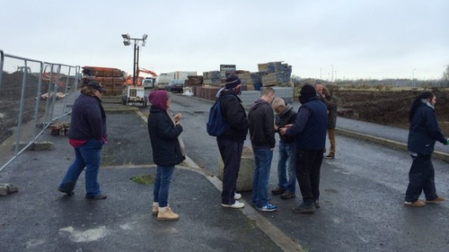 Around 20 people have gathered at the entrance of the site on Balbutcher Lane in Ballymun