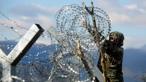 A Macedonian army soldier finishes the razor-wired fence along the border with Greece
