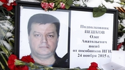 A portrait of Oleg Peshkov among flowers outside the Russian Defence Ministry building in Moscow, Russia