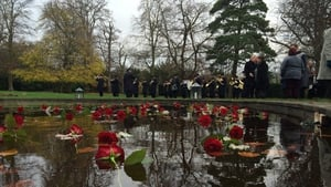 Roses are cast on the pond at Farmleigh for the missing as the  Garda Band plays
