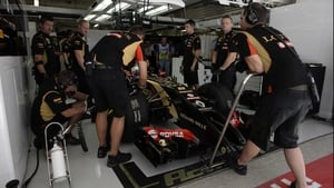 The Lotus team carry out repairs in the pits