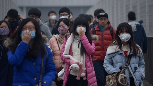 Pedestrians wearing face masks walk through heavy air pollution in Beijing