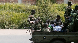 A military vehicle carrying men, who are tied up, drives through the city of Bujumbura
