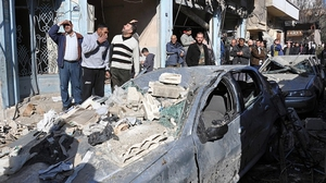 Syrians gather at the site of a car bomb explosion in Homs