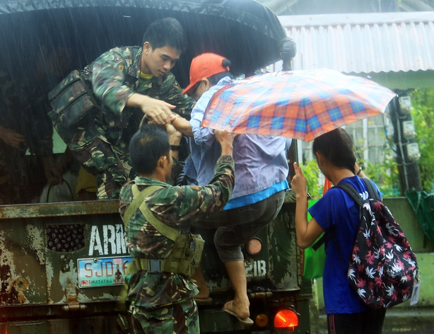 Military personnel evacuate residents from a village in the city of Legaspi
