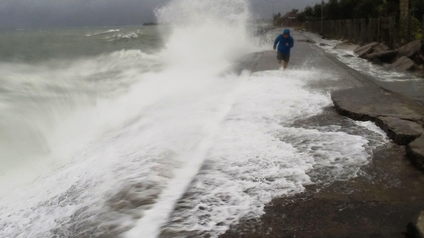 A resident walks past big waves spilling over a wall onto a coastal road in the city of Legaspi, south of Manila, as typhoon Melor approaches