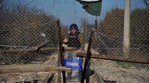 A border control policeman stands behind a fence at the borders in Idomeni village, northern Greece