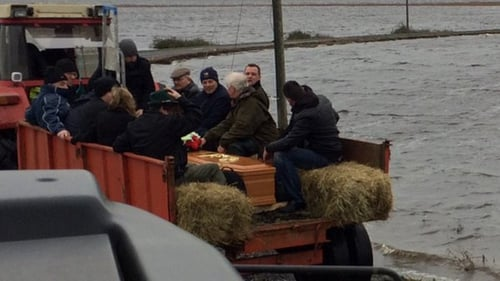 Several neighbours and friends assisted in bringing the remains of a deceased man on a tractor through the floods for burial at Saint's Island