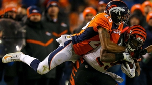 Chris Harris (No 25) of the Denver Broncos leaps on to the back of Giovani Bernard