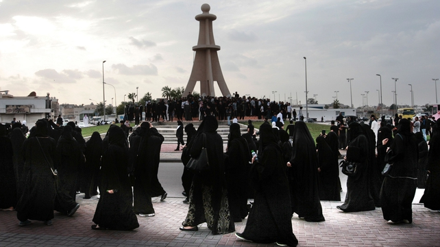 Saudi Shiite women (front) and men (back) take part in a protest in the eastern coastal city of Qatif