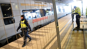 Police mount a temporary fence between domestic and international tracks at Hyllie train station in Malmo, Sweden