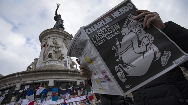 Man reads copy of Charlie Hebdo's one-year anniversary edition of last year's January attacks near a memorial site