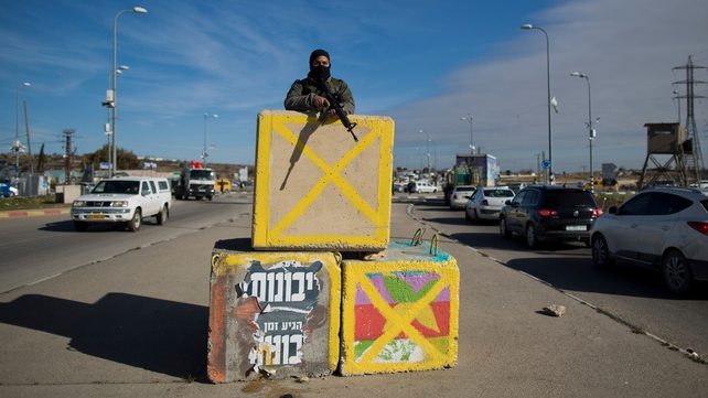 An Israeli soldier stands behind a carrier at Gush Etzion junction following an attack earlier this week