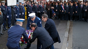 French President Francois Hollande (C, back to camera) and the mayor of Montrouge, Jean-Loup Metton (R), lay a wreath of flowers honouring policewoman Clarissa Jean-Philippe, in Montrouge, south of Paris