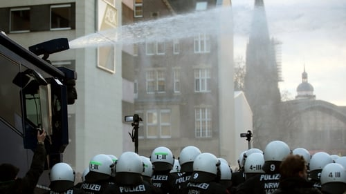 A water cannon sprays water at right-wing demonstrators next to police officers in Cologne, Germany