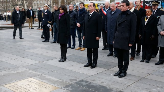 French President Francois Hollande (C), Prime Minister Manuel Valls (R) and Paris Mayor Anne Hidalgo (L) pay respect after unveiling a commemorative plaque