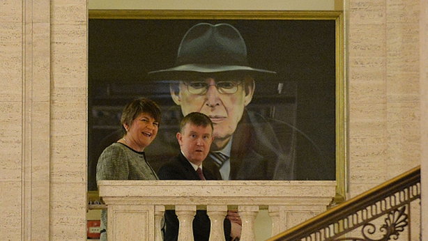 Arlene Foster walks past a painting of Ian Paisley at Stormont today