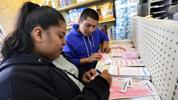 Faviola Fuentes and Miguel Tirequec fill out their numbers for the Powerball Lottery at Alcon Cut-Rate Liquor in California.