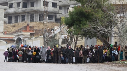 Residents of the besieged rebel-held Syrian town of Madaya wait for a convoy of aid from the Syrian Arab Red Crescent today