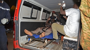 A wounded man is treated outside the hotel in Ouagadougou
