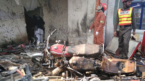 Rescue workers search the site of the suicide bomb attack