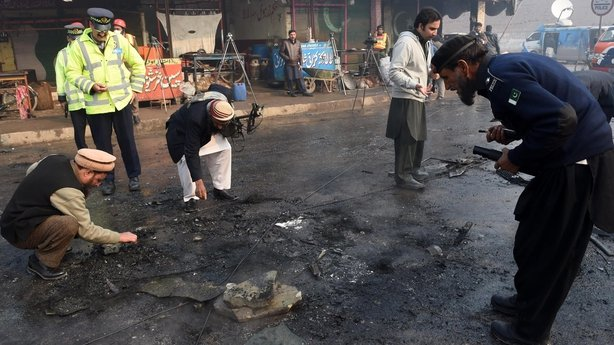 Pakistani security officials examine the site of a suicide bomb attack on the outskirts of Peshawar