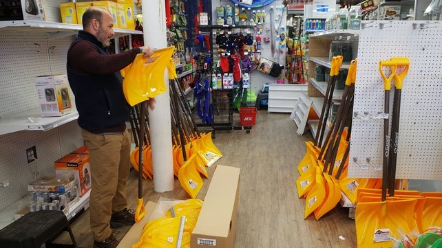 A worker in a hardware shop assembles snow shovels ahead of Washington's expected blizzard