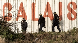 French riot police officers walk in front of a fence near the site of the Eurotunnel