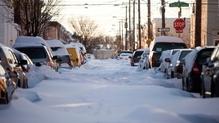 Cars sit parked on an unplowed street in Philadelphia, Pennsylvania