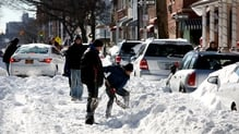 People work on digging out their cars following the snow storm in Brooklyn, New York