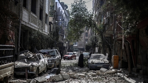Locals inspect the aftermath of an airstrike by government forces in Douma, on the outskirts of Damascus