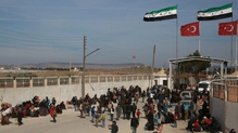 Syrians fleeing the city of Aleppo wait at the Bab al-Salama crossing on the border between Syria and Turkey