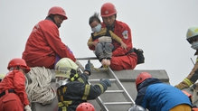Rescue personnel help a young victim at the site of a collapsed building