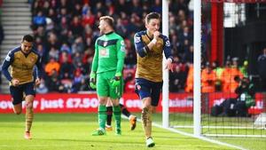 Artur Boruc looks dejected as Mesut Ozil celebrates his goal