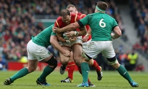Jamie Roberts of Wales is tackled by Jack McGrath and CJ Stander