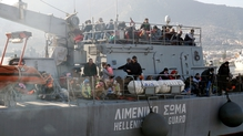 Refugees arrive aboard a coast guard ship at the port of Lesbos island