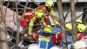 Rescue workers are seen in protective clothing