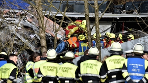 An injured passenger is removed from the crumbled trains