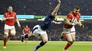Wales' Gareth Davies scores a try despite the efforts of Scotland's Tommy Seymour
