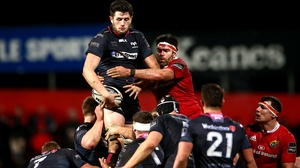 Ospreys' Rory Thornton and Billy Holland of Munster rise in battle for possession