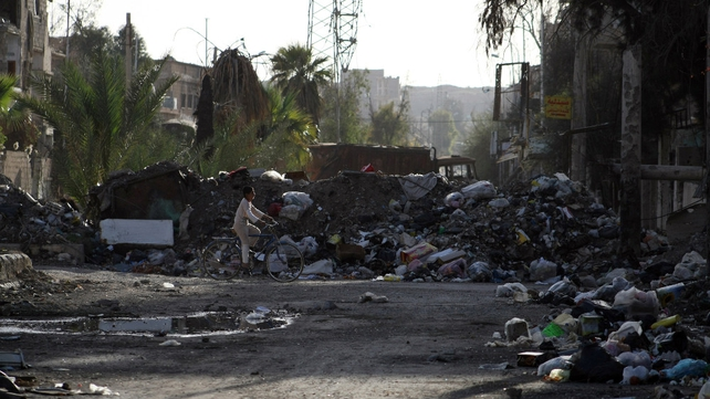 A child cycles by piles of rubbish in the besieged town of Deir ez-Zor