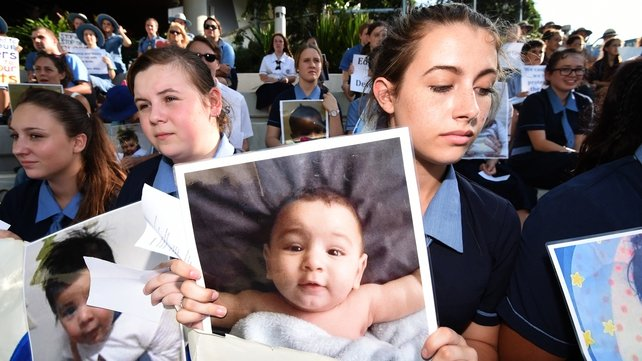Students hold photographs of baby Asha during a protest outside the Lady Cilento Children's Hospital in Brisbane