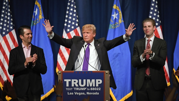 Donald Trump speaks as his sons Donald Trump Jr (L) and Eric Trump (R) look on during the caucus