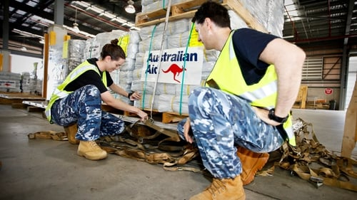 Members of the Royal Australian Air Force prepare aid to be delivered to the cyclone-hit areas of Fiji